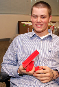 3D ThinkLink Lab student Caleb Dujmovic from Freestate ChalleNGe Academy with a cell phone stand he created
