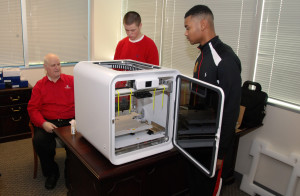 YouthQuest Director of Instruction Tom Meeks  sets up a new CubePro 3D printer with 3DThinkLink Lab students Caleb Dujmovic and Christopher Coleman.