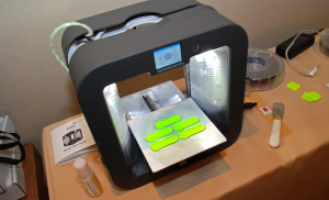 A Cube 3 printer makes a batch of key chain tags designed by students in YouthQuest 's 3D printing workshops at the National Society of Black Engineers Convention in Anaheim March 26, 2015