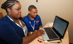 Two students in a YouthQuest workshop at the National Society of Black Engineers Convention in Anaheim work on a design for a 3D-printed tag