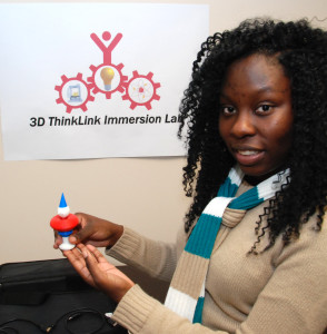 South Carolina Youth ChalleNGe Academy graduate Sherquana Adams holds one of her 3D-printed creations in YouthQuest's 3D ThinkLink immersion lab August 2014