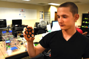 Freestate ChalleNGe Academy Cadet David Kelly holds a frame for a fidget spinner he 3D printed during immersion training week in YouthQuest's 3D ThinkLink Creativity Lab June 2017