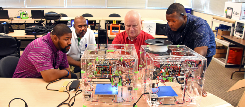 Freestate's Jonathan Brown, Capital Guardian's Keith Hammond, YouthQuest Director of Instruction Tom Meeks and Freestate's Jamarr Dennis work with a JellyBox 3D printer during 3D ThinkLink Teacher Training on Sept. 27, 2017.