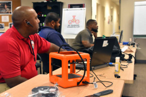 Capital Guardian's Keith Hammond and Freestate's Jonathan Brown and Jamarr Dennis learn about the M3D Micro 3D printer during 3D ThinkLink Teacher Training on Sept. 26, 2017.