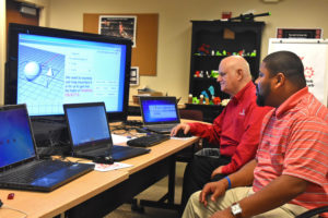 YouthQuest Director of Instruction, Tom Meeks. show Moment of Inspiration 3D design software to Jonathan Brown from Maryland's Freestate ChalleNGe Academy during 3D ThinkLink Teacher Training Week in September, 2017.