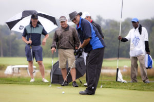 YouthQuest Co-Founder Allen Cage putts in the rain at the golf tournament August 7, 2017.