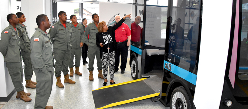 Customer Engagement Manager Tracye Johnson points to the 3D-printed Accessible Olli vehicle during a Vocational Orientation tour of Local Motors in National Harbor, Maryland for 3D ThinkLink students from DC's Capital Guardian Youth ChalleNGe Academy on April 19, 2018.